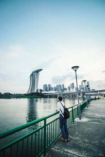 Woman standing on suspension bridge over river