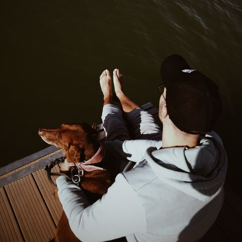 High angle view of man with dog sitting by water