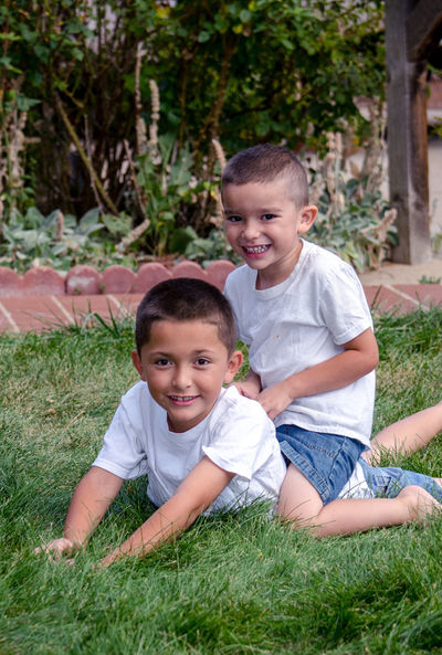 two young brothers pose for a photo outdoors Bonding Boys Brothers Cheerful Child Childhood Cute Day Elementary Age Grass Happiness Hispanic Kidsphotography Lifestyles Looking At Camera Nature Outdoors People Portrait Posing Real People Sitting Smiling Togetherness Two People