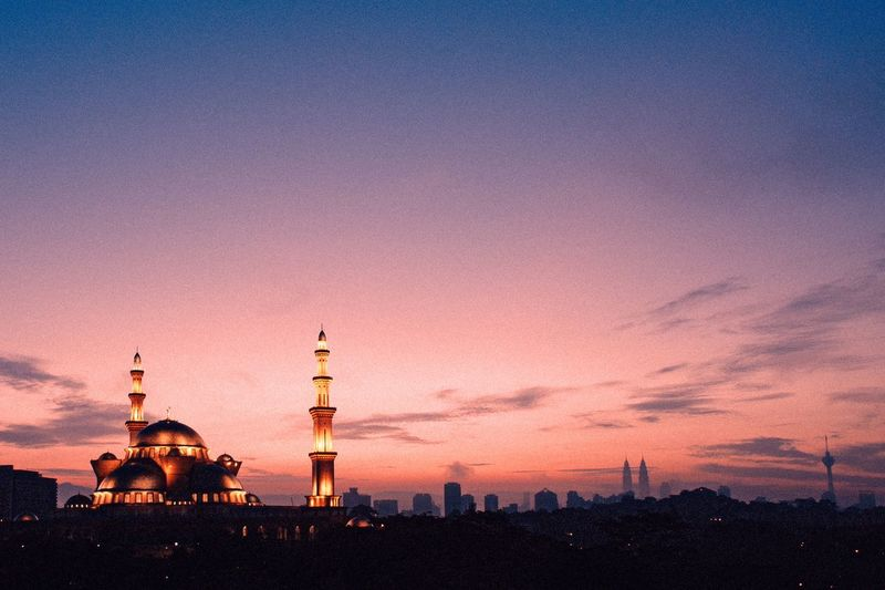 Mosque lit up at dusk against cloudy sky