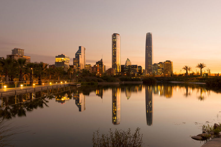 Illuminated city by lake against sky during sunset