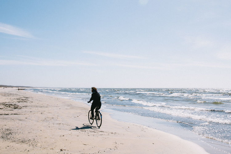 Rear view of woman riding bicycle at beach against sky