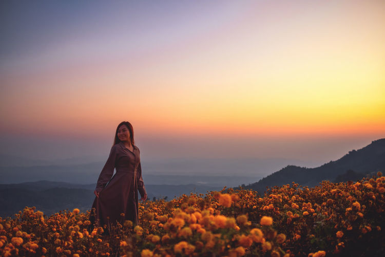 Woman standing by flowering plants against orange sky