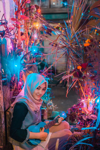 Portrait Of Smiling Young Woman Wearing Hijab Playing Ukulele By Decorations At Night
