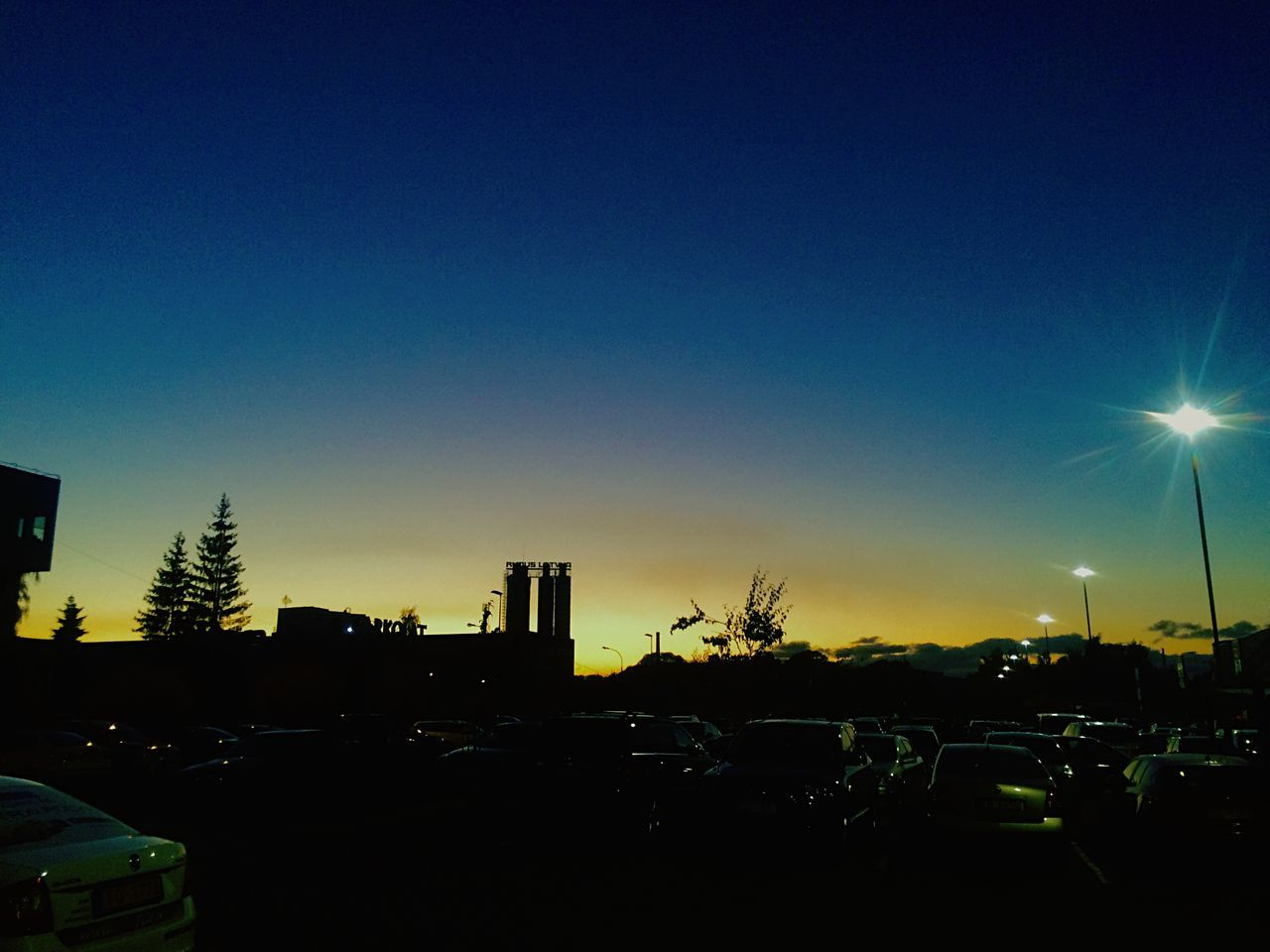 car, land vehicle, transportation, building exterior, mode of transport, built structure, no people, architecture, blue, clear sky, sky, sunset, city, outdoors, illuminated, tree, nature, day