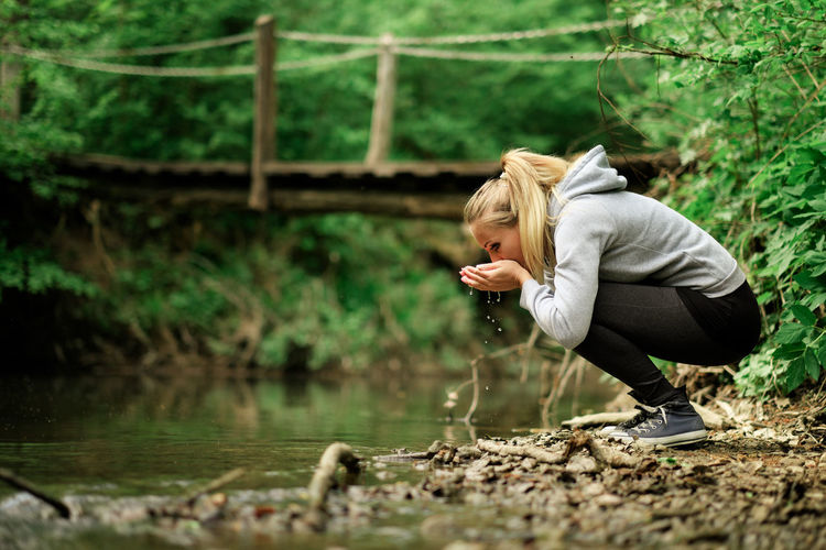 Nature Adult Blond Hair Casual Clothing Crouching Forest Nature One Person Outdoors Real People Stream - Flowing Water Survival Survivor Tree Water Women Young Adult