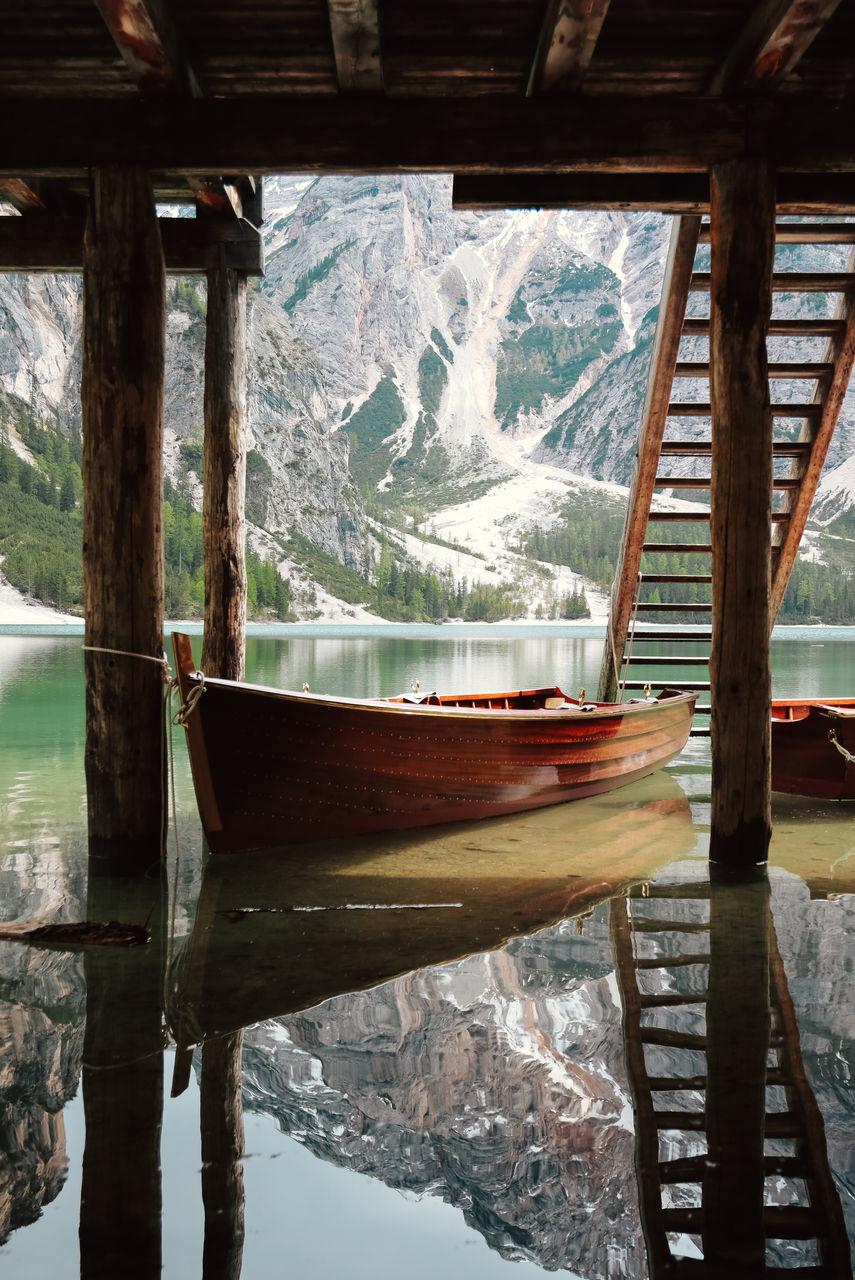 Boat Moored Below Pier In Calm Lake
