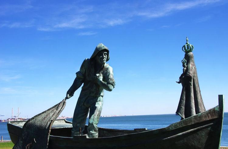 memorial bronze statues of fishermen and Our Lady Blue Human Representation Nautical Vessel Representation Sculpture Sea Sky Statue Transportation Travel Water