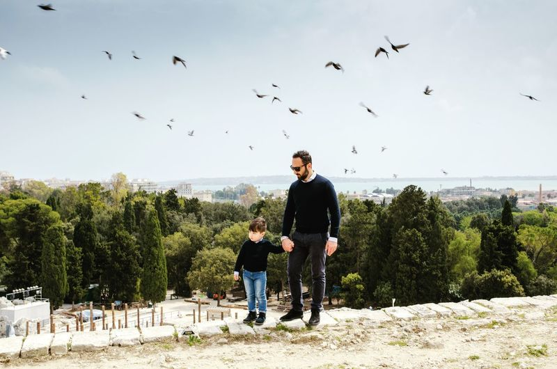 Father and son standing on footpath against birds