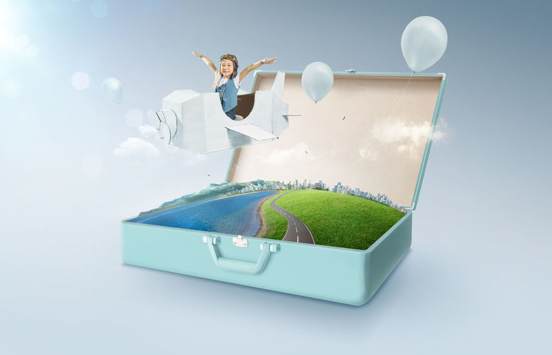 Digital composite image of girl flying in paper airplane over suitcase with city street