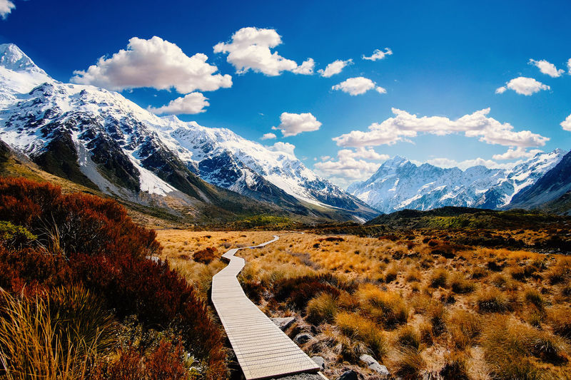 Boardwalk leading towards mountains against sky during winter
