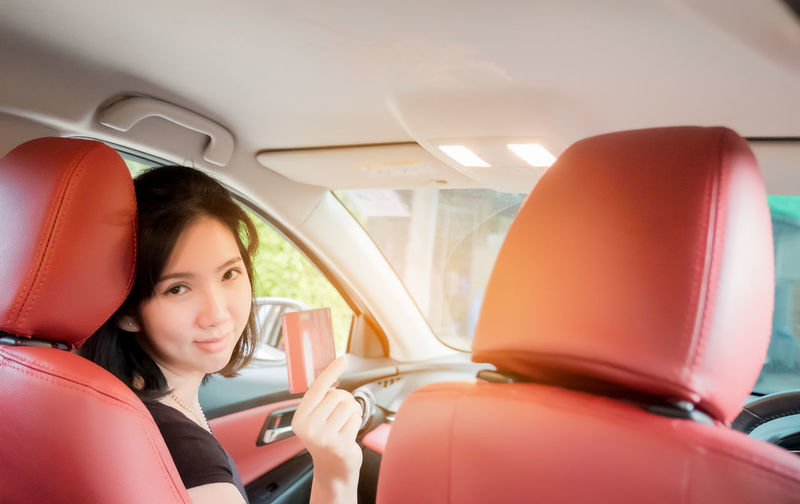 Happy woman thai sitting inside her new car showing credit card, Women Asia Mode Of Transportation Transportation Car Motor Vehicle Land Vehicle Real People One Person Vehicle Interior Women Lifestyles Portrait Travel Young Women Headshot Young Adult Leisure Activity Adult Sitting Looking At Camera Outdoors