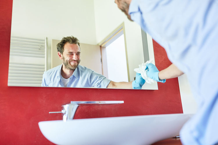 Smiling man cleaning mirror while standing by sink at home