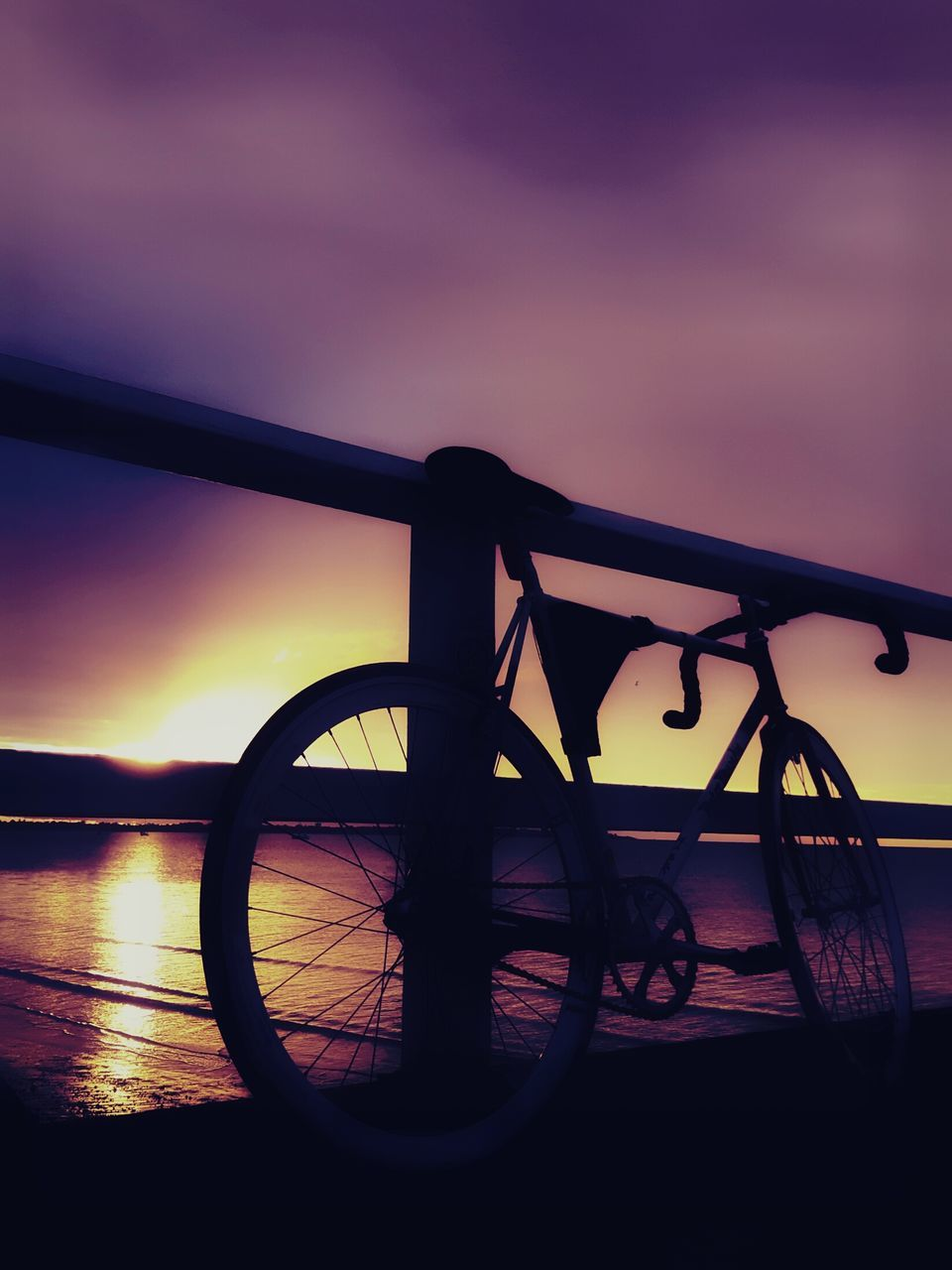 sunset, bicycle, transportation, sky, mode of transport, silhouette, stationary, land vehicle, nature, no people, outdoors, scenics, water, bicycle rack, beauty in nature, day, close-up