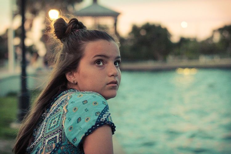 Close-up of thoughtful girl sitting at swimming pool during sunset
