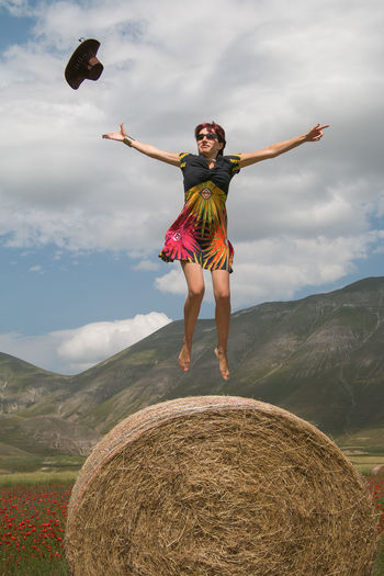 Full Length Of Woman Jumping Over Hay Bale Against Sky