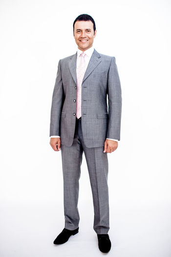 Man in classic suit on the white background. Studio shot. Classic Adult Business Business Person Businessman Formalwear Front View Full Length Full Suit Indoors  Looking At Camera Males  Men Menswear One Person Portrait Smiling Standing Studio Shot Style Suit Well-dressed White White Background White Backround