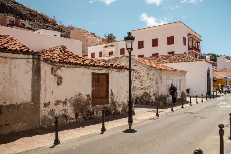 Residential buildings by street in town against sky