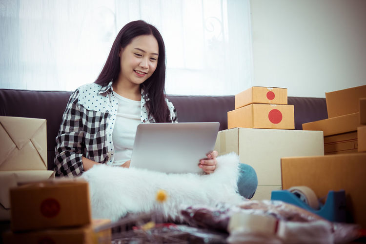 Smiling young woman using phone while sitting at home