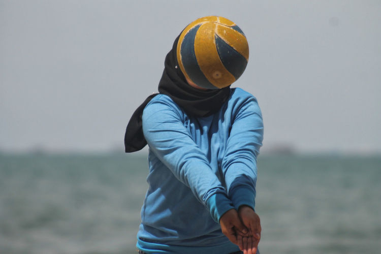 Woman playing volleyball against sky