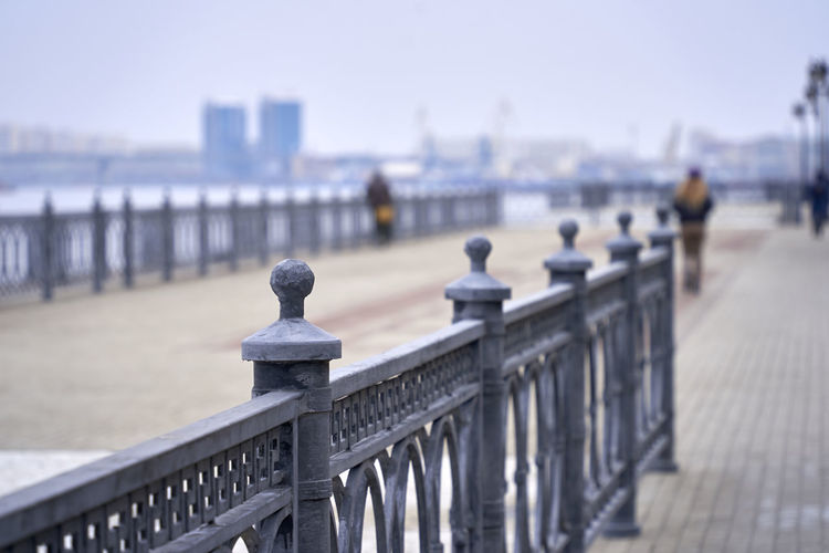 Railing on pier by sea against sky in city