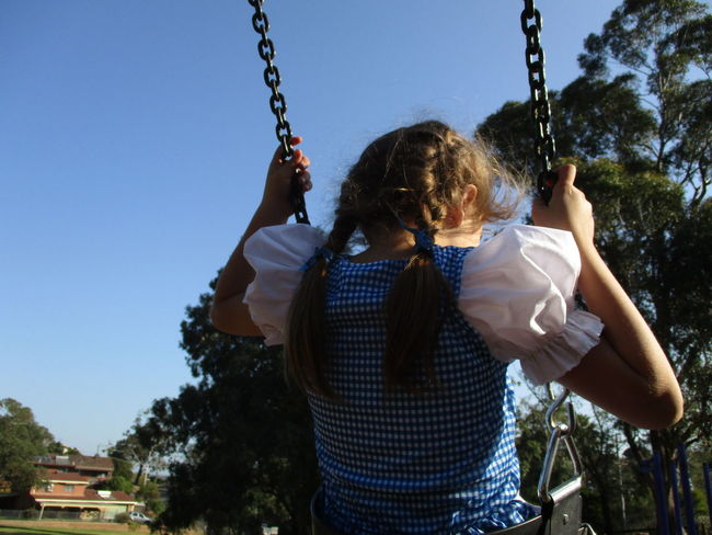 Braids Braided Hair Brunette Chain Childhood Clear Sky Day Dorothy Fun Gingham Girls Holding Leisure Activity Lifestyles Outdoors People Playground Playing Real People Rear View Sky Swing Swings Tree Vichy