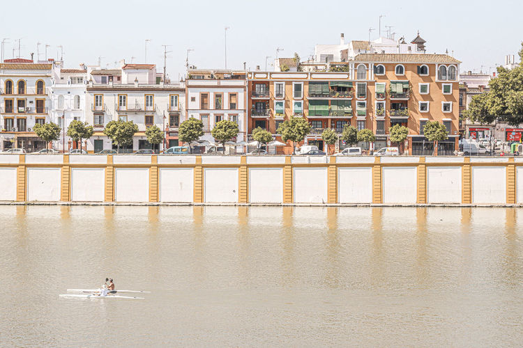 Men practicing canoeing on the river with colonial-style houses at triana