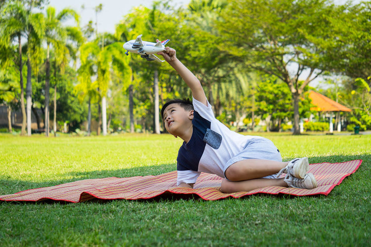 Adult Day Full Length Grass Leisure Activity Lifestyles Lying Down Nature One Person Outdoors Park - Man Made Space People Real People Tree Young Adult Young Women