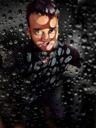 Portrait of wet man standing in rain