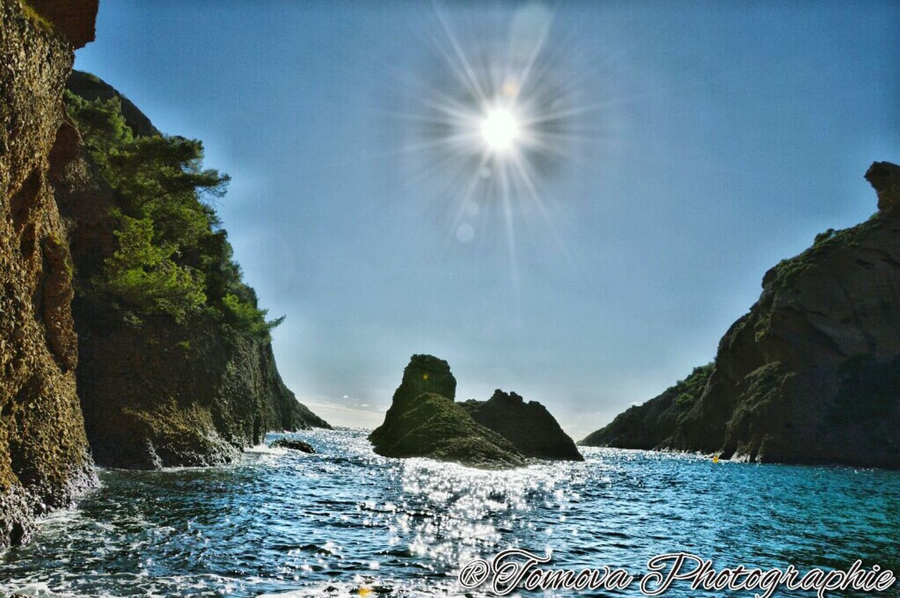 lens flare, nature, beauty in nature, water, sunlight, sea, tranquility, sun, scenics, no people, tranquil scene, outdoors, day, sky, blue, mountain, clear sky, scenery