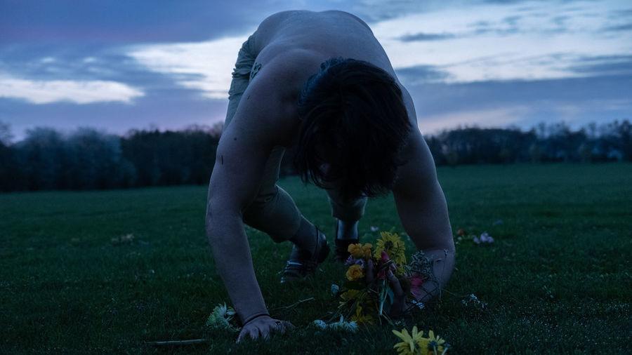 Shirtless man holding flowers on grassy land at sunset