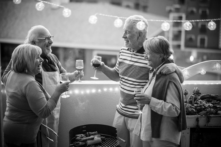 Happy senior couples toasting wine
