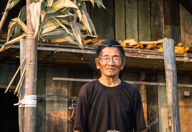 Senior man standing against hut