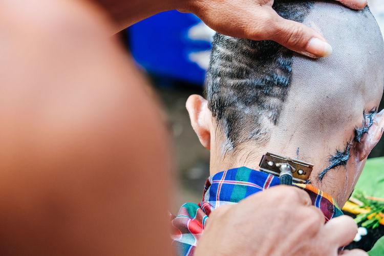 Close-up of man shaving head of boy