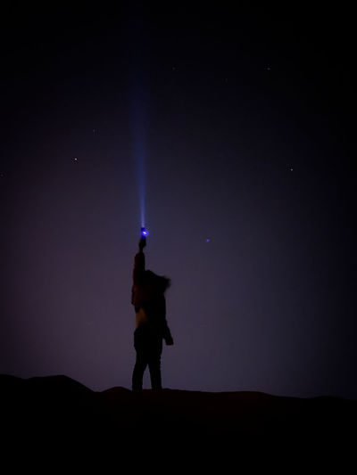 Silhouette man standing on illuminated field against sky at night