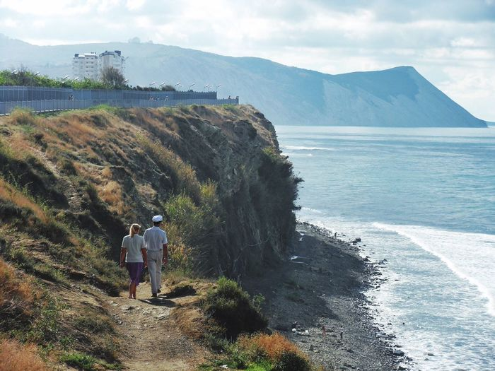 Rear view of man and woman walking on hill by sea against sky