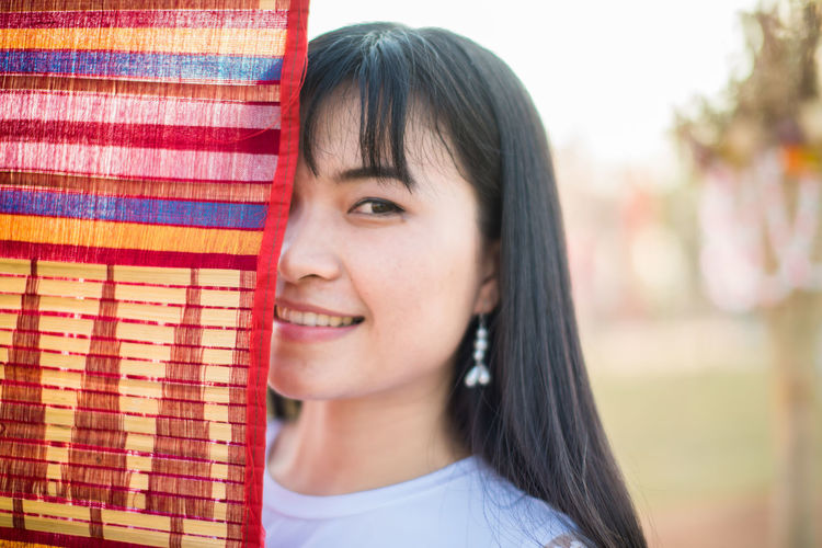 Close-up portrait of smiling young woman standing by colorful flag