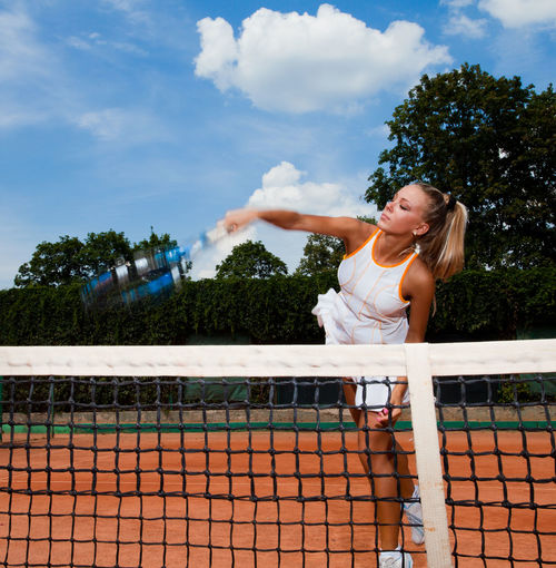 Young sporty woman hitting a ball over the net on the court Girls Tennis Hair Sky Playing Women Tree Child Sport Day Court Outdoors Childhood Hairstyle Blond Hair Females Lifestyles Tennis Racket One Person Cloud - Sky Human Arm Real People Leisure Activity