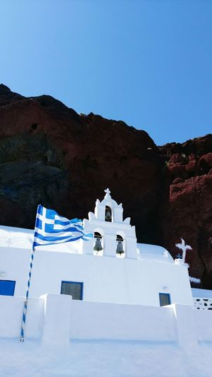 Low angle view of greek flag by bell tower against clear sky at santorini