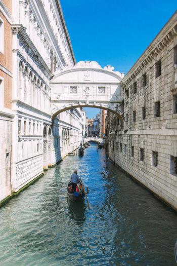 Man in gondola on grand canal against bridge of sighs