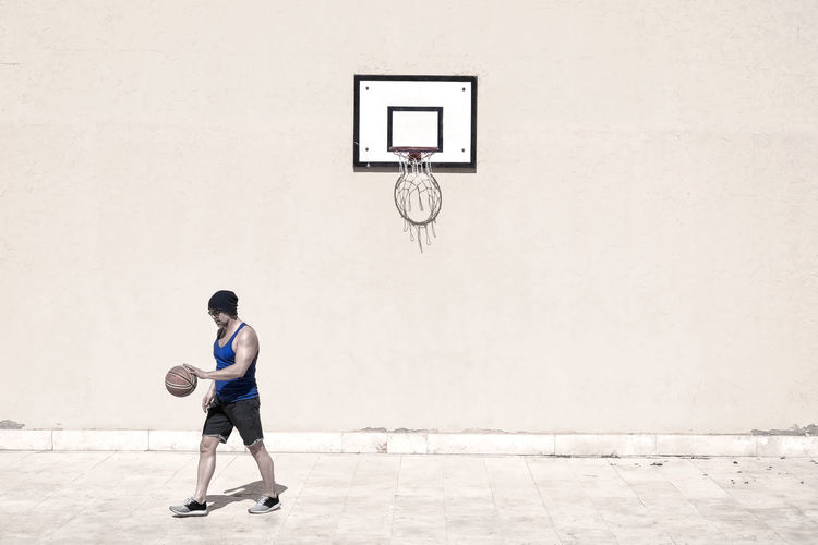 Man playing with basketball on court during sunny day