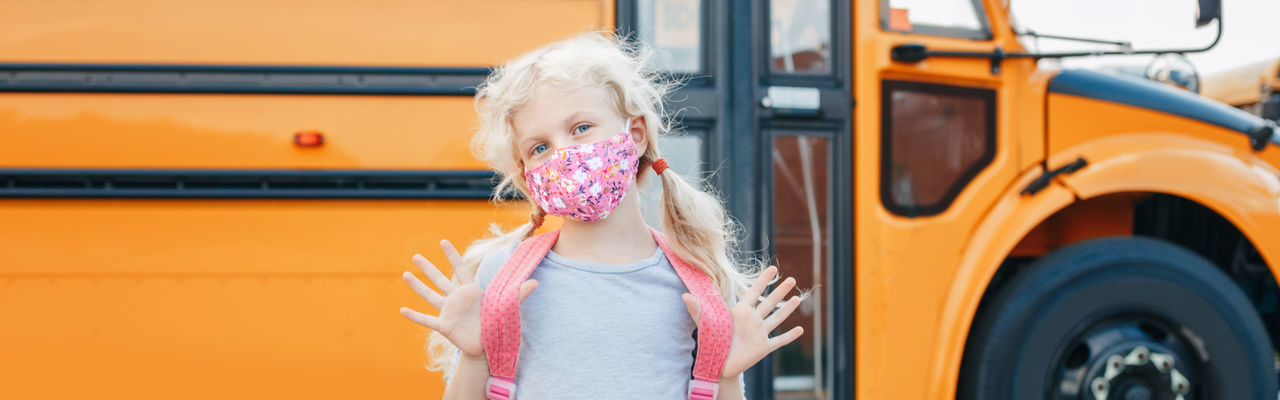 Caucasian girl in face mask standing by yellow school bus. new normal. web banner header.
