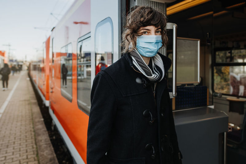 Portrait woman wearing mask standing by train on railroad station platform