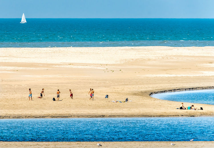 High angle view of children playing on sand at beach during sunny day