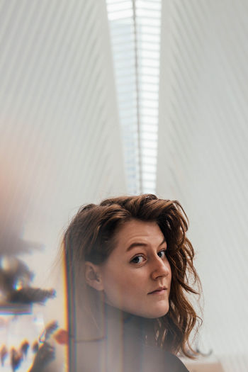 Close-up portrait of young woman with long brown hair against ceiling