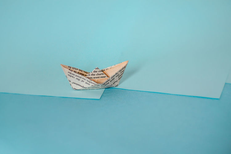 Low angle view of paper floating on water against blue background