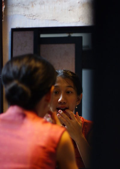 Rear View Of Woman Applying Make-Up In Front Of Mirror