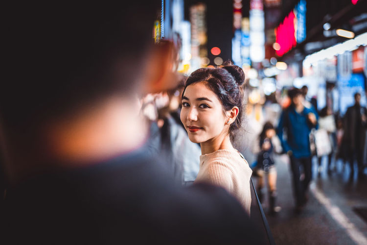 Portrait of beautiful woman standing on street at night