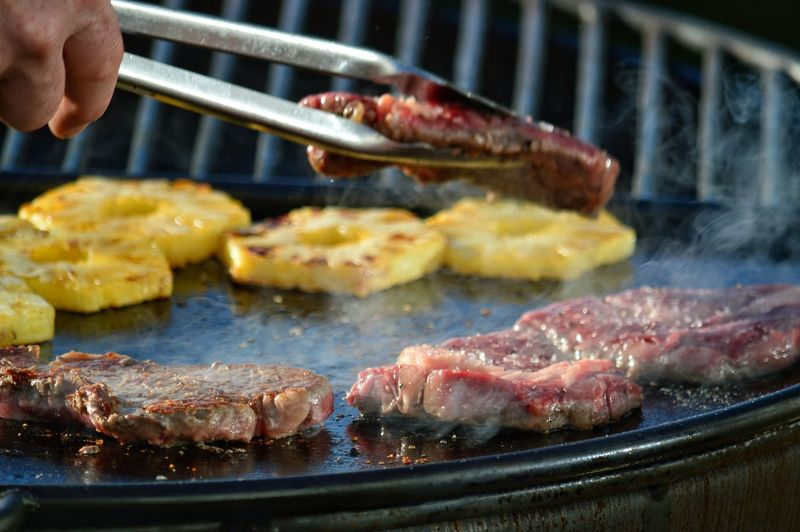 Cropped Image Of Hand Cooking Meat On Barbecue Grill