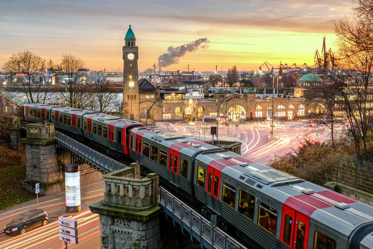 High angle view of train in city against sky at sunset